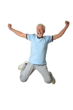 Senior man jumping on a white background