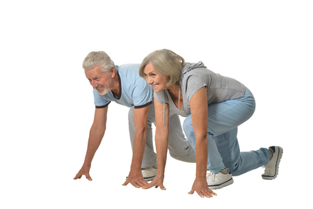 senior men: Portrait of Senior Couple Exercising On White Background Stock Photo