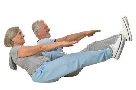 Portrait of Senior Couple Exercising On White Background Foto de archivo