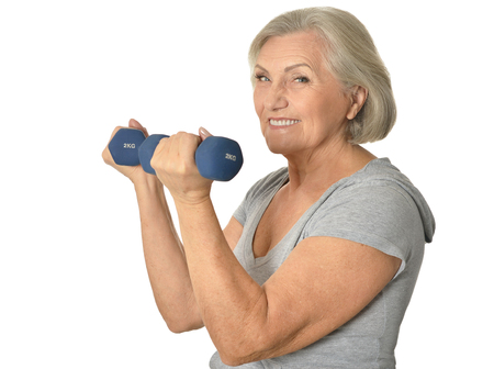 senior woman exercising: Senior woman exercising with dumbbells on white background
