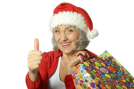 look up: Happy senior woman with shopping bags and thumb up