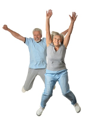 Senior couple jumping  on a white background
