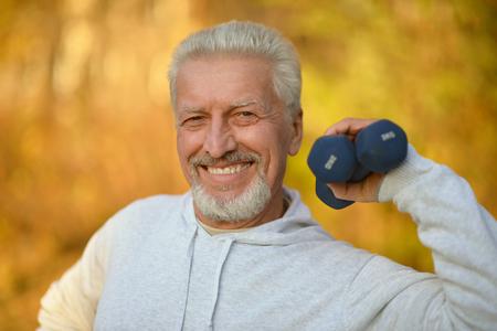 medical man: Elderly man exercising with dumbbells in autumn park