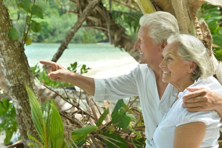 old sign: Beautiful happy elderly couple rest at tropical resort,man pointing by his hand
