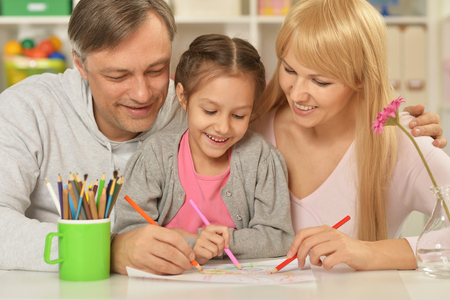 kindergarten education: Portrait of happy family painting at home
