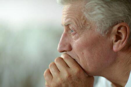 dolorous: Portrait of a sad senior man at home