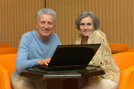 orange chairs: Mature couple sitting with laptop in orange chairs