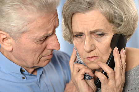 alling: Portrait of a sick senior woman calling doctor with her  husband Stock Photo