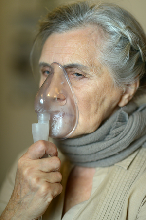inhalation: Portrait of elderly woman with flu inhalation Stock Photo