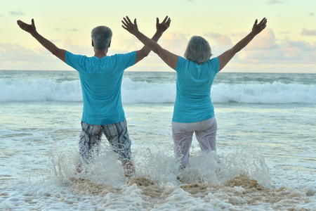 Beautiful happy elderly couple rest at tropical resort with hands up