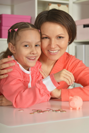 depositing: Mother and Child Daughter Putting Coins into Piggy Bank