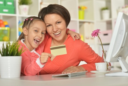 a study: Portrait of a little girl  with mother doing shopping online  at home Stock Photo