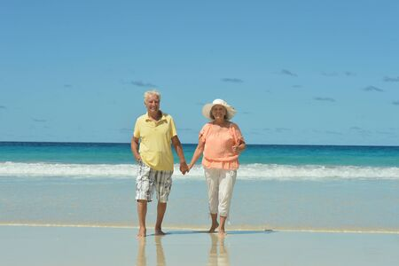 marido y mujer: Beautiful happy elderly couple on beach at tropical resort