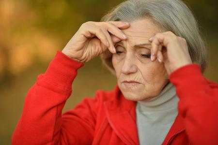 Schöne traurige alte Frau auf dem Herbsthintergrund Standard-Bild - 51081832