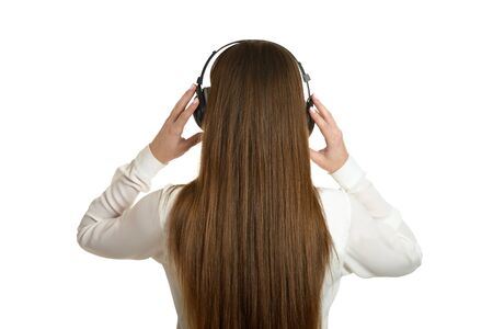 woman back: Happy beautiful girl listening to music in headphones,back view. Stock Photo