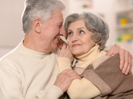 loveliness: Two elderly people sitting at home on couch Stock Photo