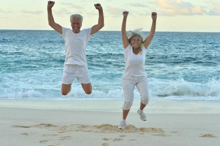 jumping: Senior pareja feliz saltando en verano en la costa