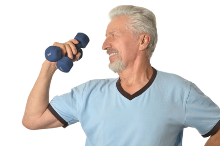 weight training: Portrait Of  Senior man Standing With Dumbbells On White Background