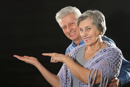 advertises: Portrait of an elderly couple advertises products on a black background Stock Photo
