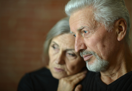 sad Mature couple near wall in the room Foto de archivo