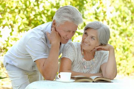 Hermosa feliz pareja de ancianos con la bebida y el libro en el verano