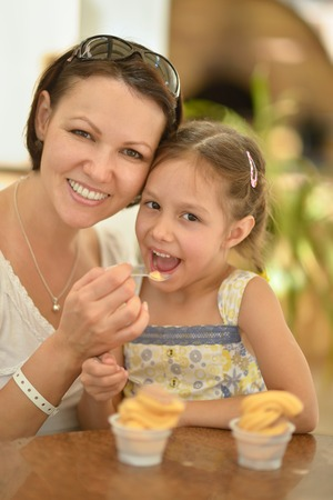 Little cute girl eating ice cream with her mother