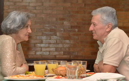 older couple: Happy mature couple eating dinner at restaurant Stock Photo