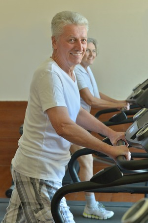 personal training: Active smiling senior couple exercising in gym Stock Photo