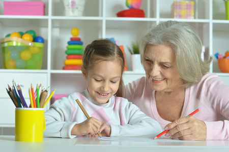 grandmother grandchild: Portrait of a happy grandmother with granddaughter drawing together Stock Photo
