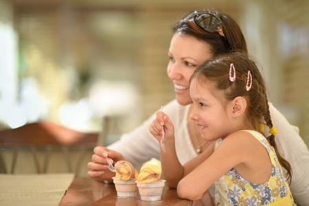 comiendo helado: La peque�a muchacha linda que come el helado con su madre