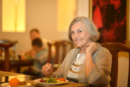 eating dinner: Senior woman having a dinner at restaurant