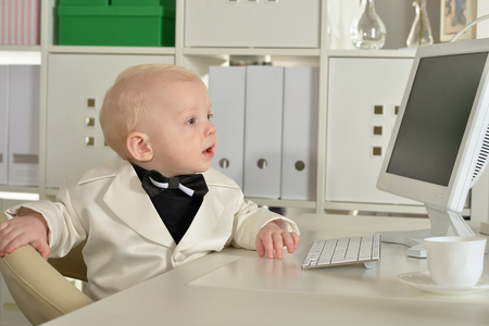 funny boy: Small cute business boy and computer in office