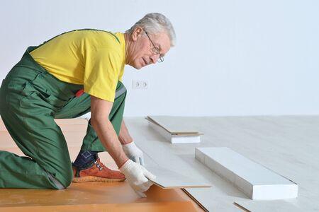 elderly man: portrait of Senior man and his grandson repairing in the room Stock Photo