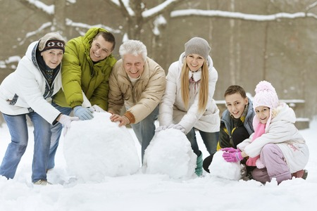 snow woman: happy young family playing in fresh snow and building snowman at beautiful sunny winter day outdoor in nature