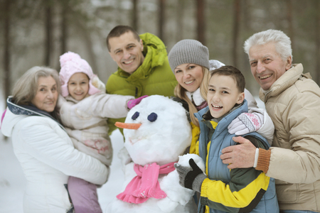 happy  family playing in fresh snow and building snowman at beautiful sunny winter day outdoor in nature