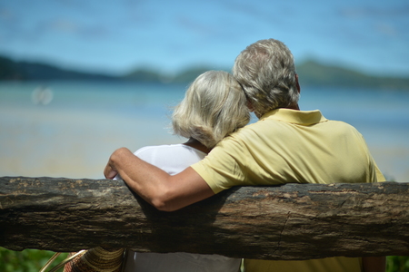 back view of man: Beautiful happy elderly couple on beach at tropical resort,back view Stock Photo