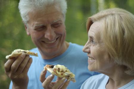 Porträt eines älteren Menschen Pizza auf die Natur zu essen