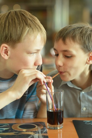 coke: Two cute boys drinking coke in cafe