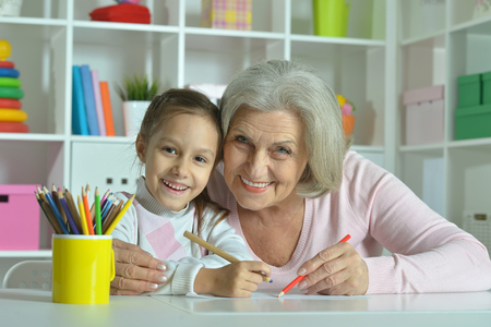 grandmother: Portrait of a happy grandmother with granddaughter drawing together Stock Photo