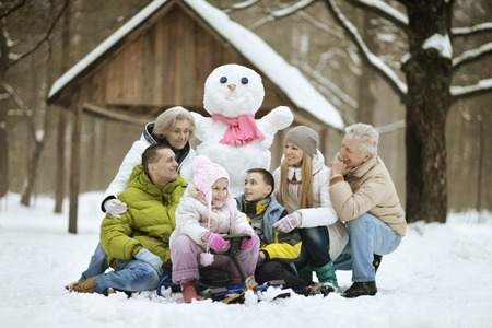 glückliche Familie im frischen Schnee spielen und Gebäude-Schneemann am schönen sonnigen Wintertag draußen in der Natur
