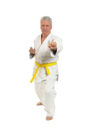 arts backgrounds: Senior man in karate pose on white background
