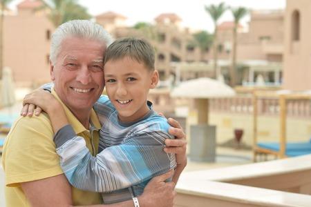 grandkid: Happy senior man with grandchild relaxing at vacation resort