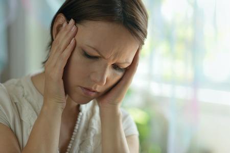 persona triste: SPortrait de una mujer enferma con dolor de cabeza en el hogar