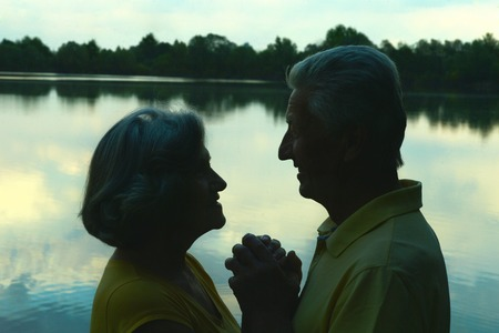 women friendship: Silhouette of an elderly couple in love at night river