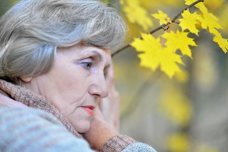 sad old woman: Nice sad old woman on the autumn background