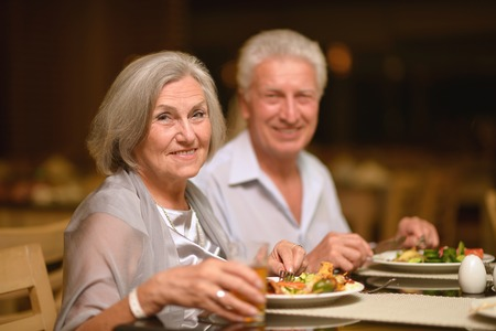 Happy mature couple eating dinner at restaurant Stock Photo