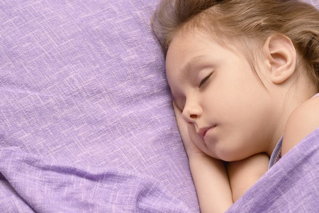 Beautiful little girl is sleeping in her bed at home Stock Photo