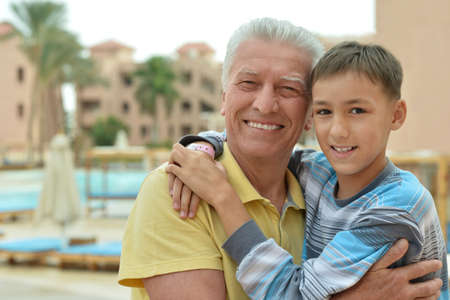 Happy senior man with grandchild relaxing at vacation resort
