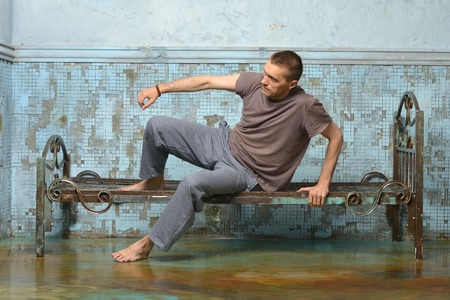 retribution: Man on the metal rusty bed in prison Stock Photo