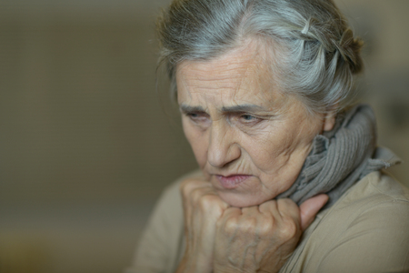 senior pain: Portrait of a sad aged woman close-up